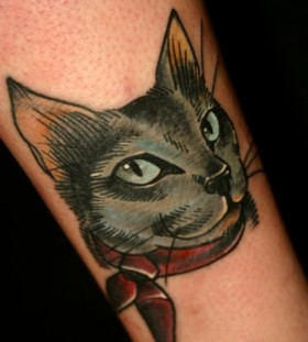 Red bow and cat tattoo on leg