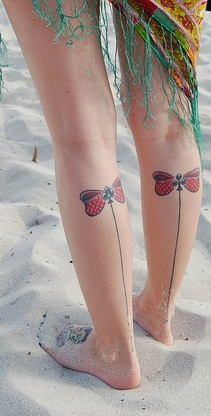 Red bow and line tattoo on leg