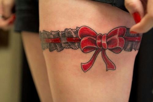 Red bow and pretty lace tattoo on leg