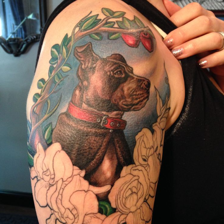Red cherries, green leafs and dog tattoo on arm