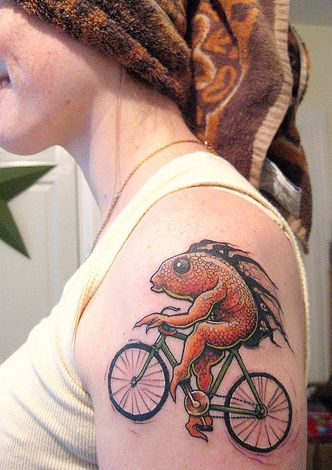 Red fish and bicycle tattoo on arm
