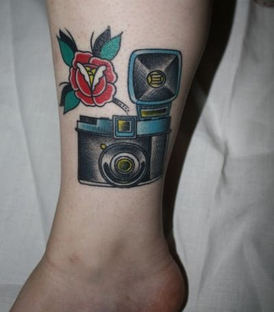 Red flower and camera tattoo on leg