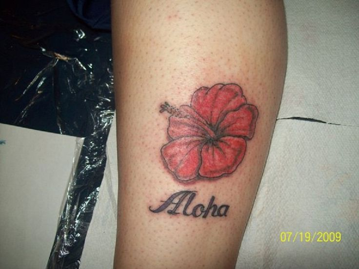 Red flower and quote tattoo on leg