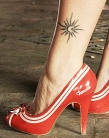 Red high-heels and sun tattoo on leg