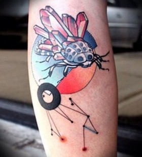 Red insect crystal tattoo on leg