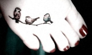 Red nails and black bird tattoo