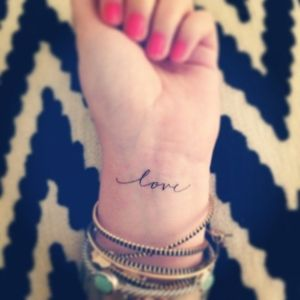 Red nails and love tattoo on arm