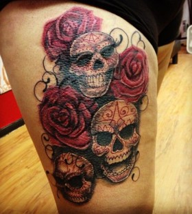 Red rose and skull tattoo on leg