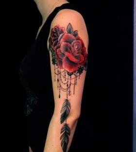 Red rose, feather and lace tattoo on arm
