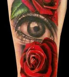 Red roses and amazing eye tattoo on arm