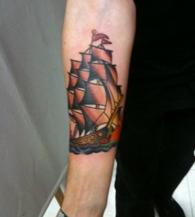 Red simple ship tattoo on arm
