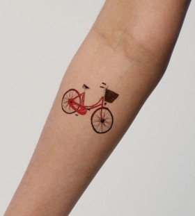 Red small lovely bicycle tattoo on arm