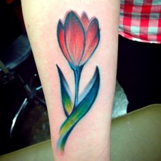 Red tulip tattoo on arm