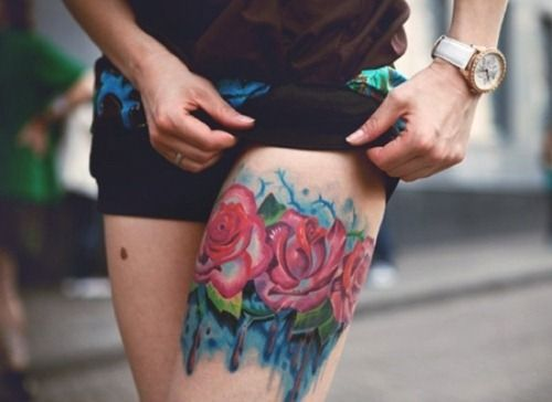 Red watercolor rose tattoo on leg