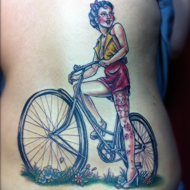 Red women's bicycle tattoo on back