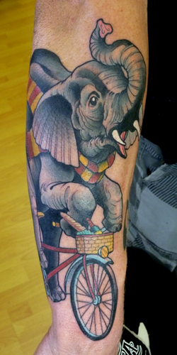 Riding elephant with bicycle tattoo on arm