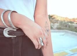 Rings, bracelet and line tattoo on arm