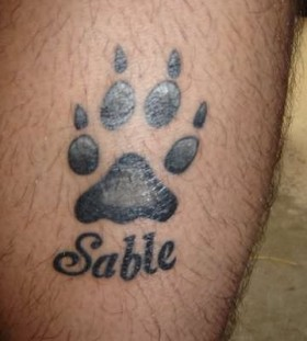 Sable pawprint dog tattoo on leg