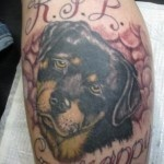 Sad black dog tattoo on arm