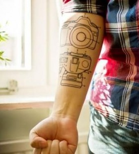 Schemes of black camera tattoo on arm
