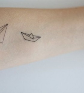 Ship and plane origami tattoo on arm