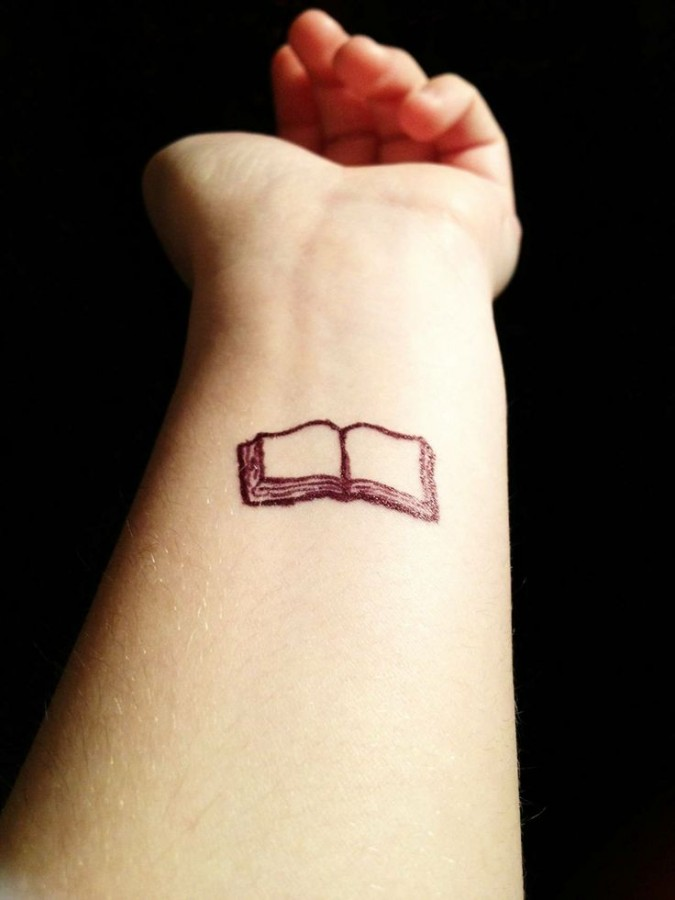 Small and pretty book tattoo on arm