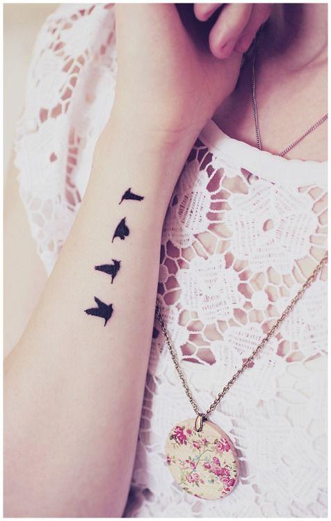 Small black birds tattoo on arm