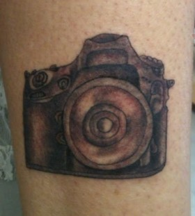 Small black camera tattoo on leg