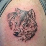 Small brown wolf tattoo on arm