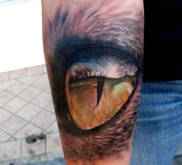 Small elephant and eye tattoo on arm
