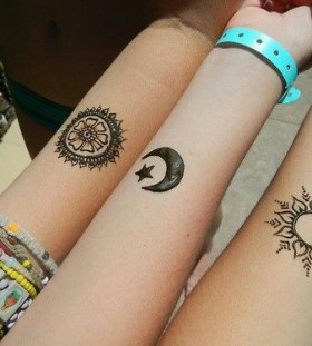 Stars, sun and moon tattoo on arm