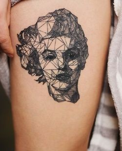 Stylish black women's face tattoo on leg