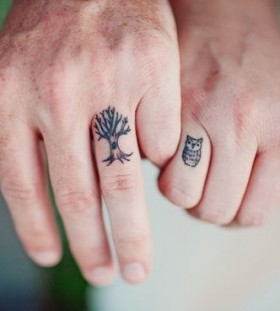 Tree and owl tattoo on finger