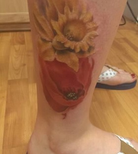 Watercolor yellow and red poppy tattoo on leg