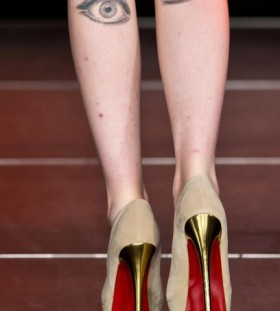Women high-heels and eye tattoo on leg