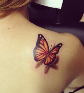 Yellow butterfly tattoo on shoulder