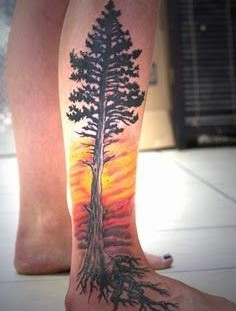 Yellow fire and tree tattoo on leg