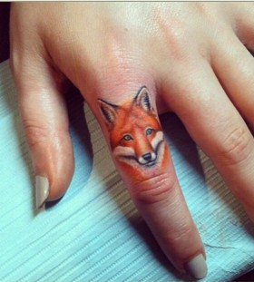 Yellow fox tattoo on finger