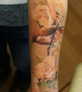 Yellow rose and brown bird tattoo on arm