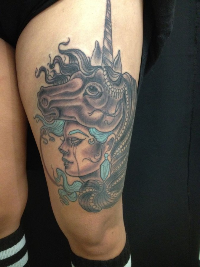 unicorn tattoo with woman face on the thigh