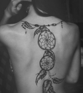 Black leafs and compass tattoo on back