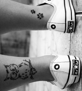 Black pawprints girl tattoo on leg