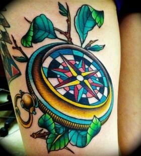 Colorful ornaments and compass tattoo on leg