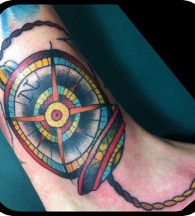 Colorful owals compass tattoo on leg