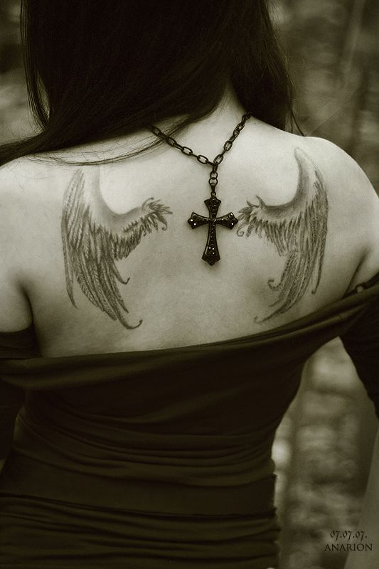 Cross and black angel tattoo on shoulder