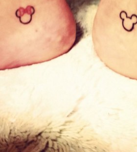 Pretty red bow with Mickey Mouse tattoo on leg