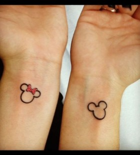 Red bow Mickey Mouse tattoo on arm