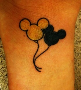 White and black Mickey Mouse tattoo on arm