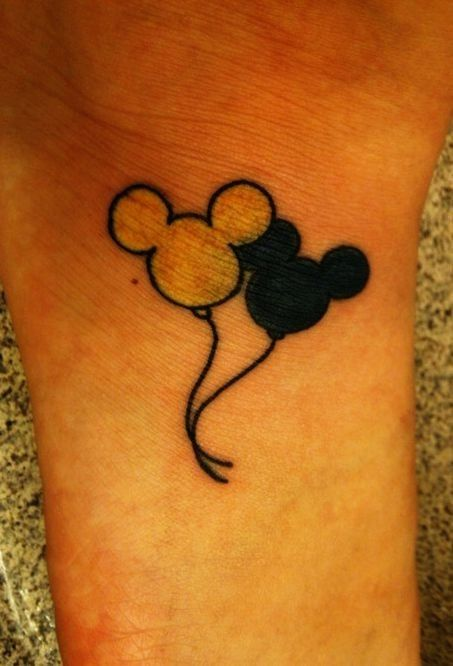 Mickey Mouse tattoo on arms