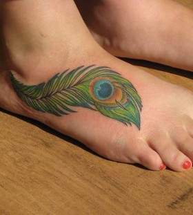 Women's leg red nails and peacock tattoo on leg